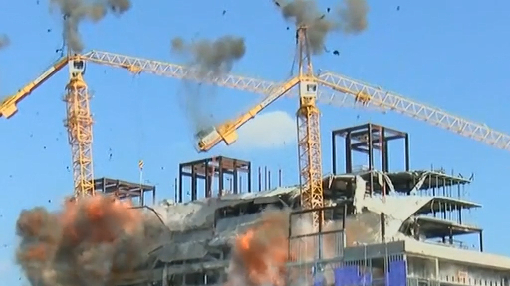 Crane left hanging after deadly hotel demolished