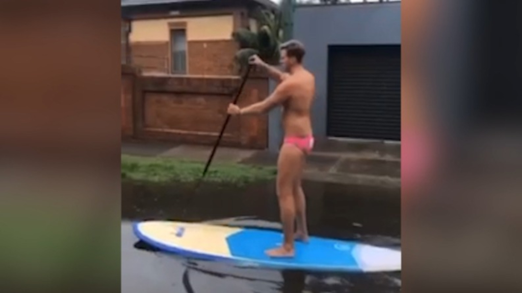 Man rides paddle board through floodwaters