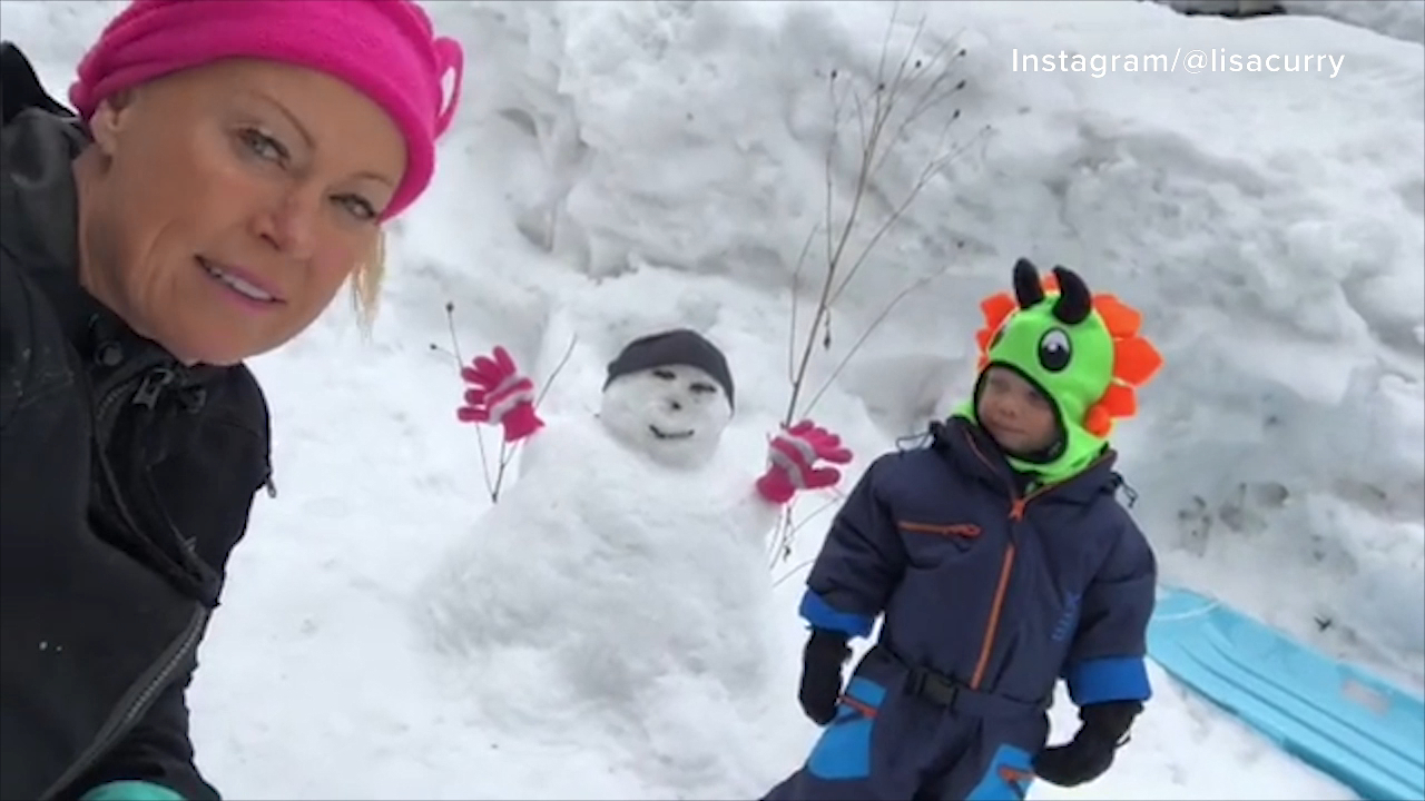 Lisa Curry playing in the snow with her grandson Flynn