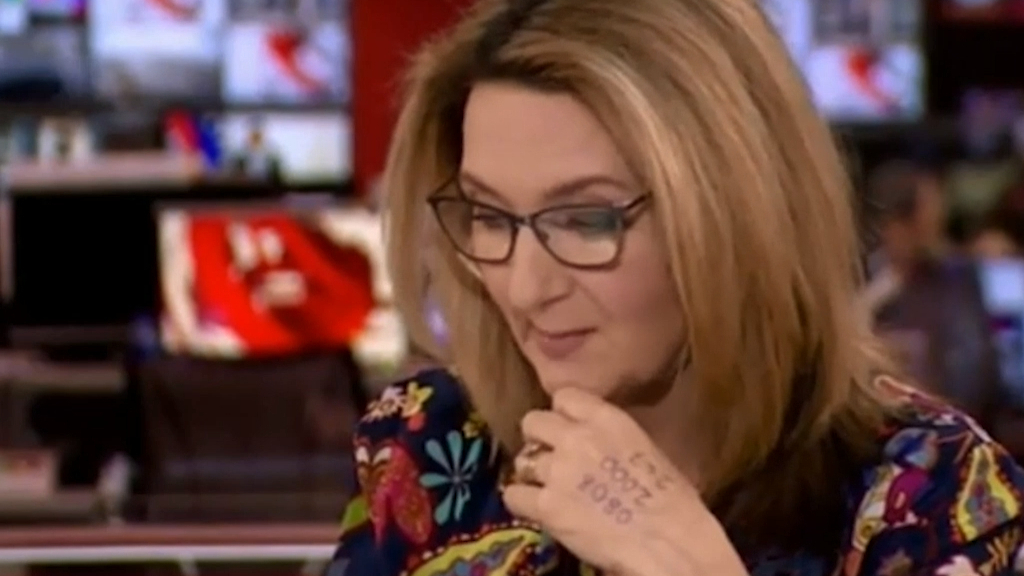 BBC News presenter hosts show with abuse helpline number written on hand