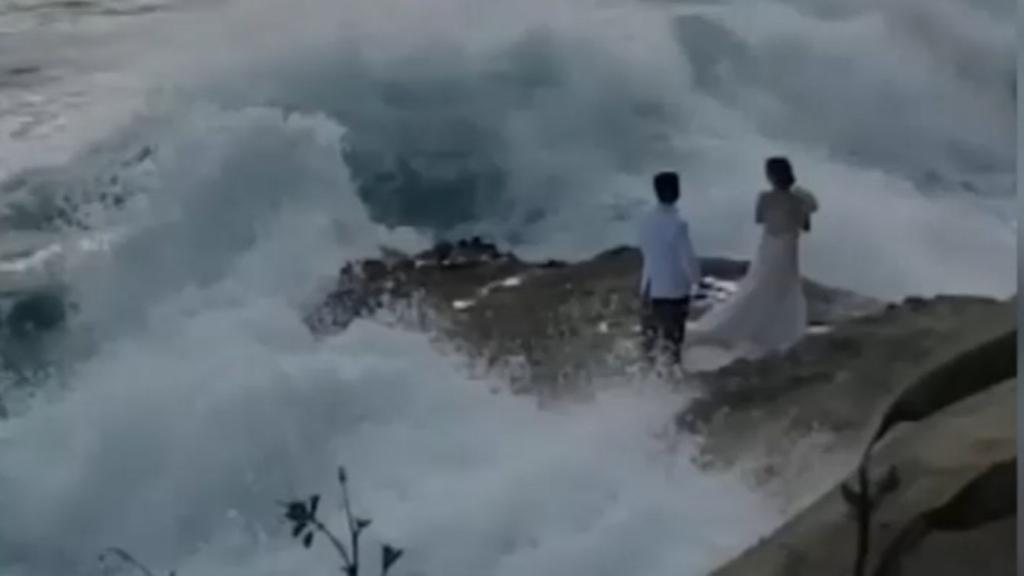 Newlyweds washed off rocks during beachside wedding shoot