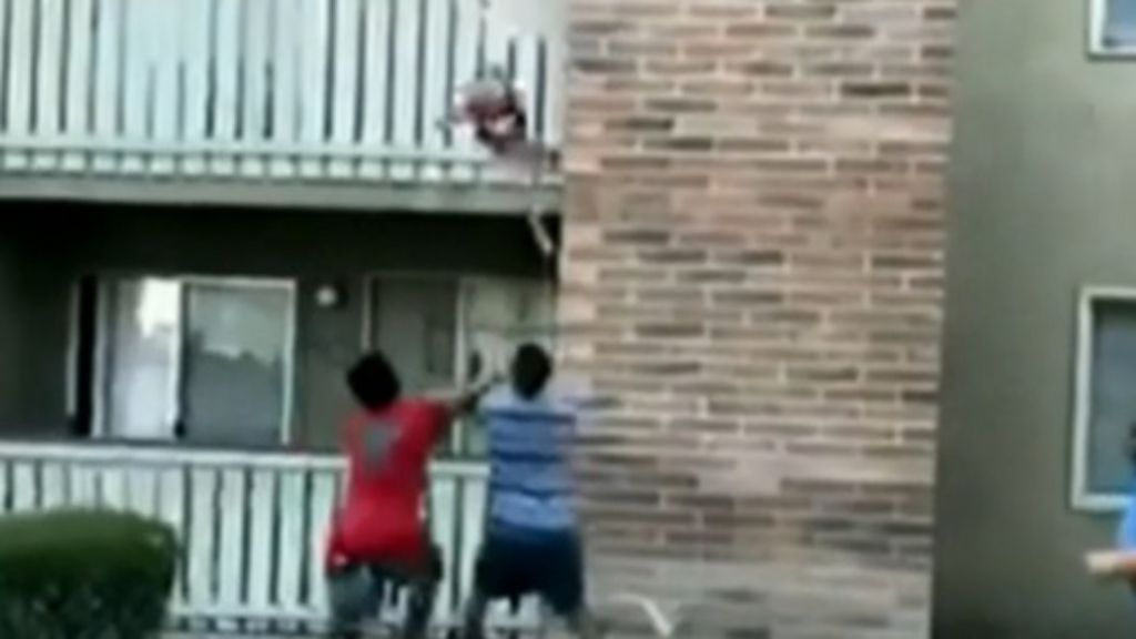 Mother throws young boy from burning building
