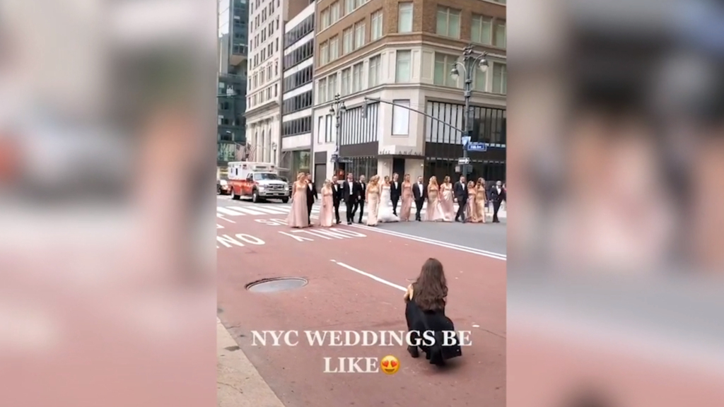 Newlyweds stage wedding photos in bus lane in New York