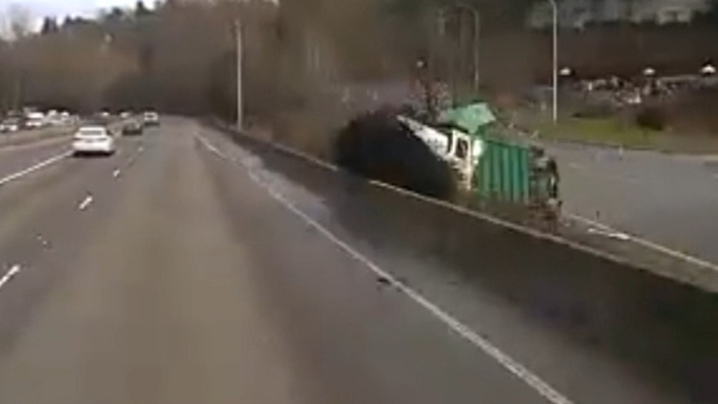Dump truck blasts through highway retaining wall in US