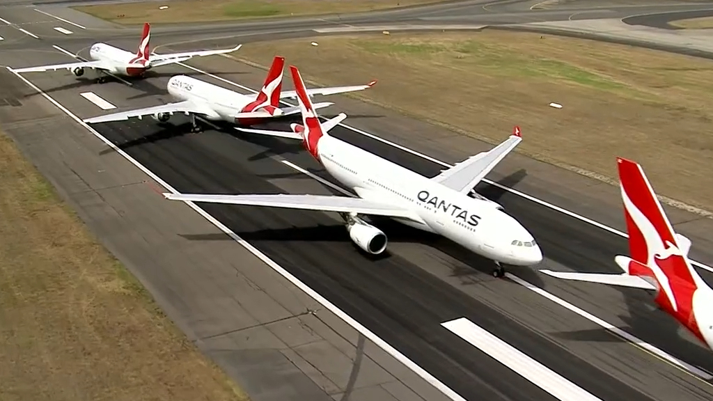 Qantas posts $1b half year loss