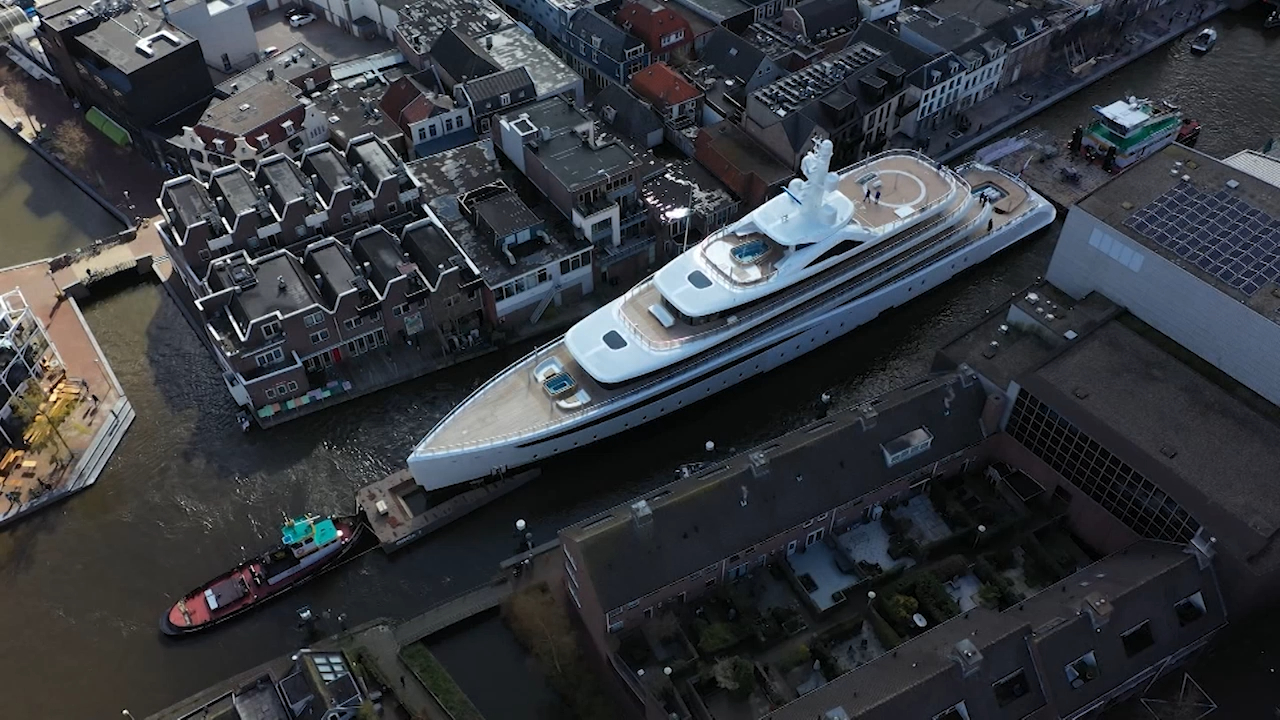 Massive superyacht squeezes through tiny canals