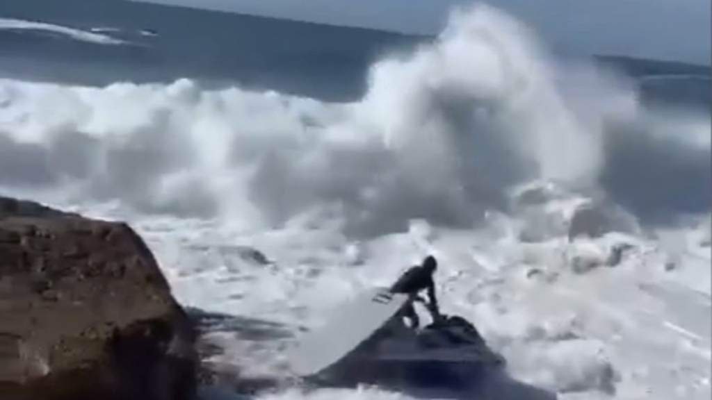 Wave washes man on jet ski into rocks