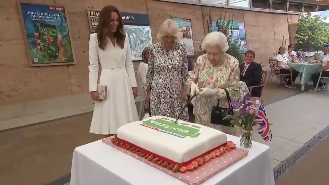 The Queen insists on cutting a cake with a ceremonial sword