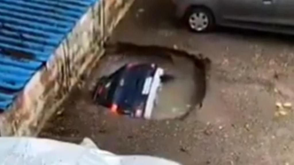 Car slowly swallowed by carpark sinkhole